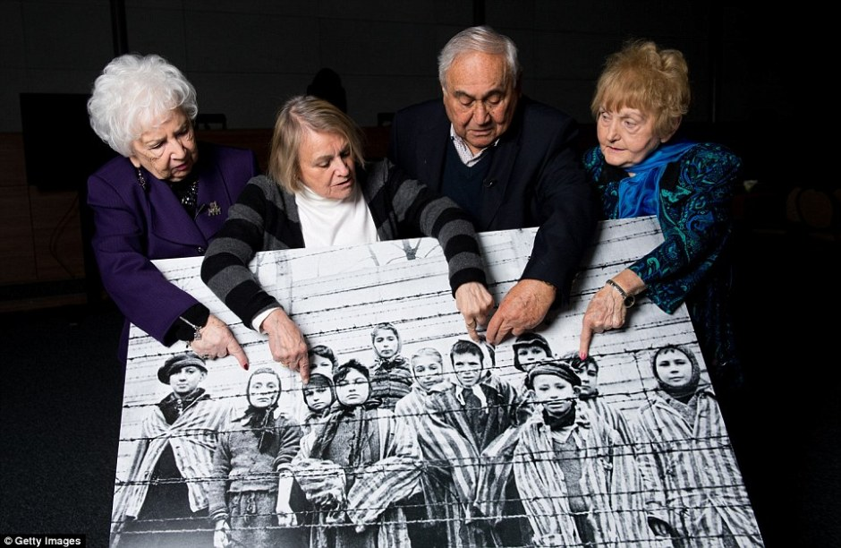 On the 70th anniversary of the liberation of Auschwitz, a group of survivors hold up and point to a picture of themselves, which was taken the day the camp was freed by the Soviet army @GettyImages