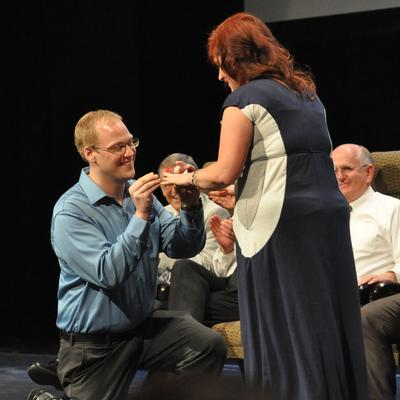 Neil Westover slips ring onto Denise Pons finger (Choir director Mack Wilberg can be seen smiling in the background). Photo courtesy Deb Gheris